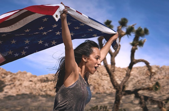Girl waving flag in desert