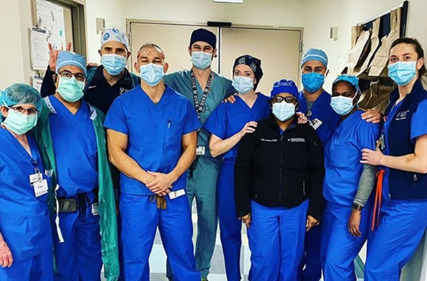 Group of clinicians wearing blue scrubs and face masks