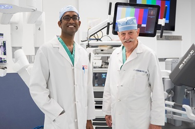 Portrait of Dr. Pavan Atluri and Dr. Clark Hargrove in an operating room with the daVinci robot