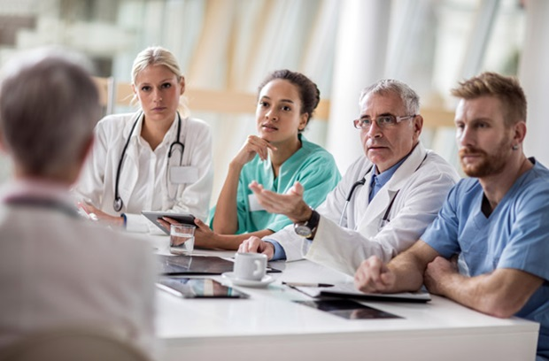 stock photo of physicians talking at table