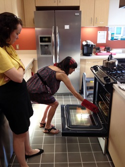Women taking pan out of oven at Transplant House - guest chef program