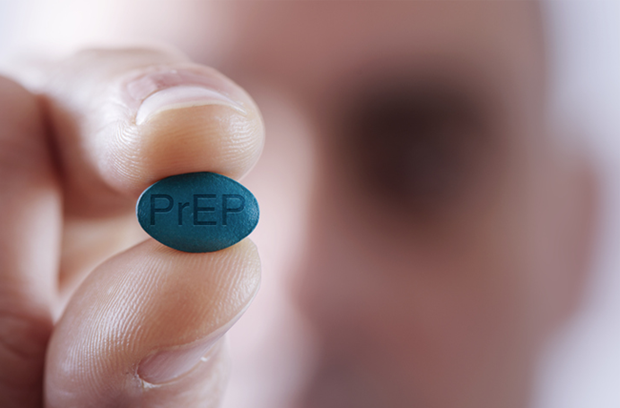 blurry_man_in_background_holds_blue_prEP_pill_for_HIV_prevention