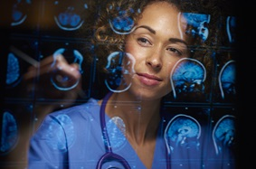 a female doctor or surgeon is analyzing the digitally generated scans of a human brain