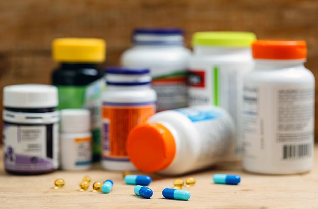 Various pills on a table in front of eight supplement bottles