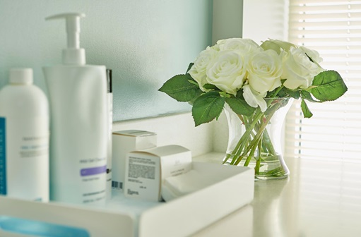 Bathroom counter with skin care products and white flowers
