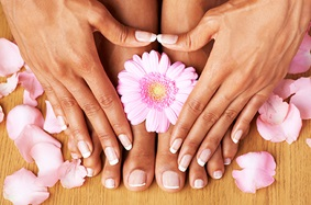 female_hands_touching_toes_with_manicured_nails_on_wooden_floor_with_pink_flowers_and_flower_petals