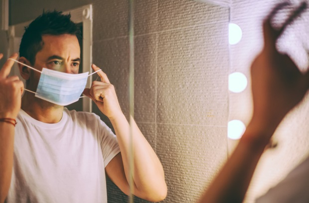 Man putting on a face mask while looking in the mirror