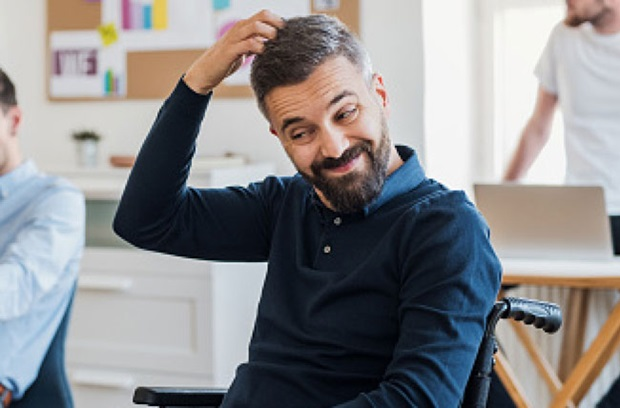 middle_aged_man_wearing_blue_shirt_with_brown_hair_sits_in_wheel_chair_scratching_head