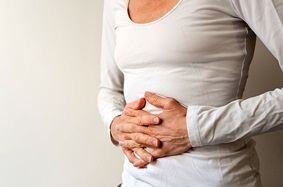 Older woman holding stomach in discomfort