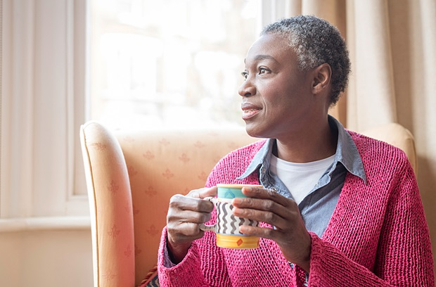 Older woman wearing a sweater while looking out the window and drinking coffee