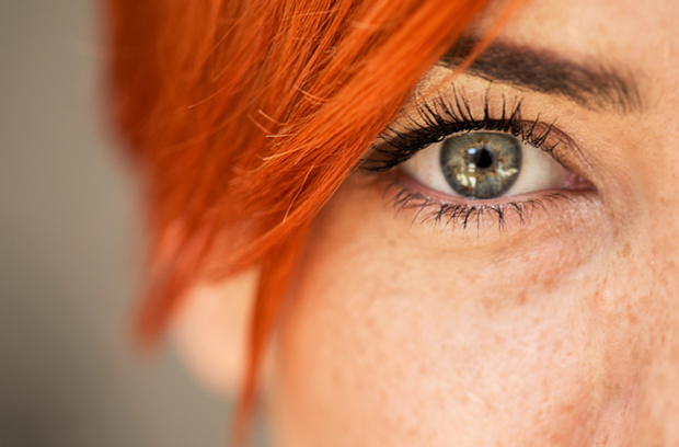 close_up_of_young_adult_woman_with_red_hair_showing_left_eye_blue_green_eye