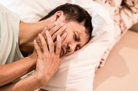 TMJ Pain Male Holding Face In Bed