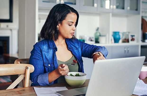A young woman checking her watch while eating a salad and working on her computer from home.