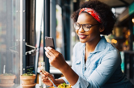 Young woman looking at her phone while eating a salad
