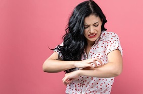 young_adult_woman_black_hair_scratching_arm_making_face_pink_background