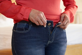 woman trying to button her jeans