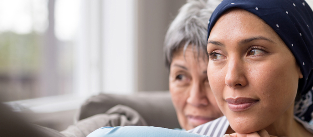 A mother and adult daughter are sitting on the couch looking out a window. The mother hugs her daughter, who is wearing a head covering.
