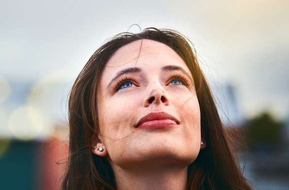 Young woman with a hopeful look, her face is pointed skyward
