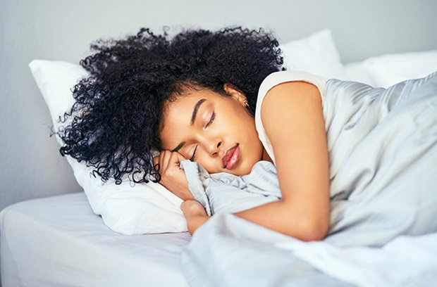 brown_skinned_young_woman_sleeping_in_bed_cuddled_with_grey_comforter
