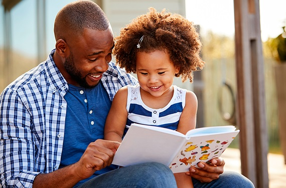 Dad and daughter laughing while reading a children's book