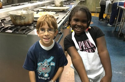 Children from David Bradley Children's Bereavement Program cooking in commercial kitchen and smiling