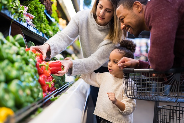 Family selecting produce at a grocery store