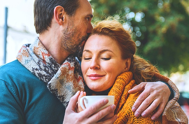middle aged men and women share a hug together as man holds coffee cup outside