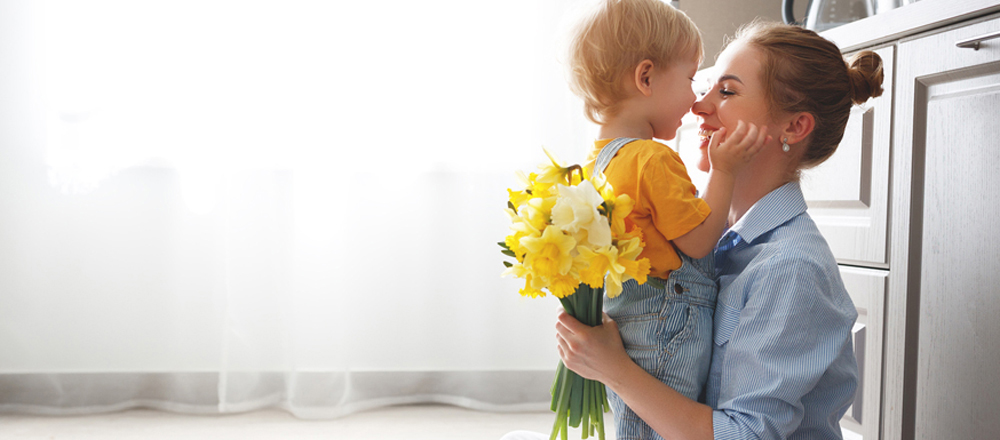 Mom holding flowers while hugging child