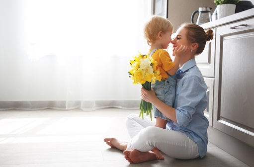 Mom sitting on the ground in kitchen hugging child