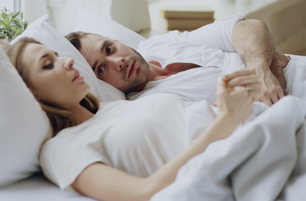 Young_woman_and_man_lay_in_bed_side_by_side_wearing_white_looking_sad