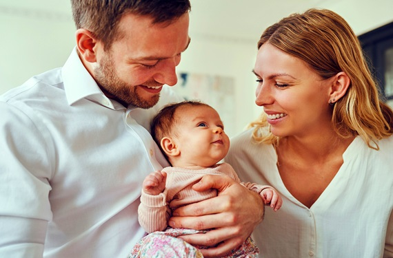 Young mom and dad smiling while holding newborn daughter
