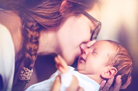 young_mom_wearing_glasses_with_braided_hair_kisses_new_born_baby