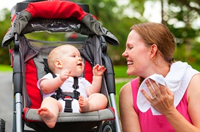 Woman smiles at baby in stroller after a run