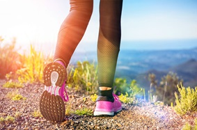Woman's legs and feet shown walking on a mountain path