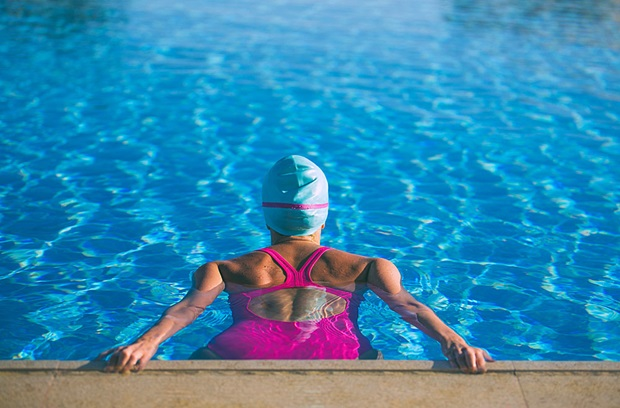 Female swimmer in pink bathing suit getting ready to start workout
