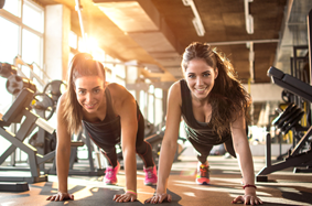 two young girls doing push ups on gym floor in between rows of exercise equipment smiling as rays of sun shine down on them from outside