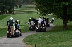 Golfers and golf carts on a golf course
