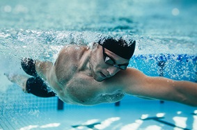 young_adult_man_swimming_in_pool_wearing_googles_and_head_swimming_cap