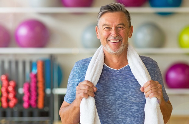 older man holding towel around neck while at the gym