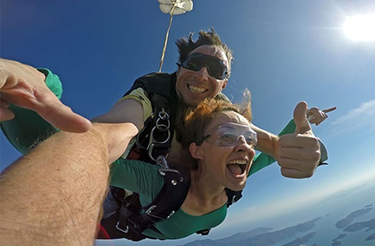 Skydivers in mid-air smiling at camera