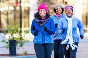 Three middle-aged African-American women walking outside in winter.