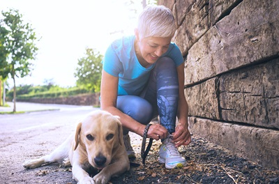 Older woman with dog tying shoe