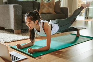 A woman working out in her home in front of a laptop.