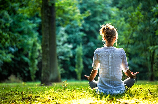 Woman sitting on the ground meditating surrounded by trees