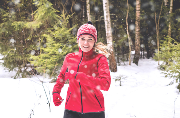 young_woman_running_outside_in_snowy_woods
