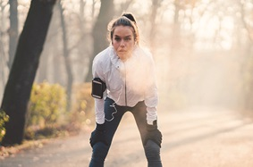 young_woman_wearing_white_jacket_with_iphone_strapped_to_arm_and_earbuds_in_stops_outside_in_woods_by_tree_to_catch_breath_during_run