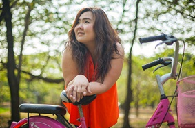 Young woman leaning on the seat of her bicycle while thinking