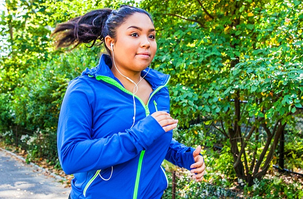Young woman with ponytail running outdoors in the spring