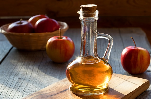 A small bottle of apple cider vinegar surrounded by apples