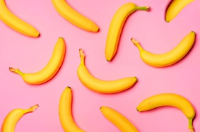 11 unpeeled loose bananas arranged on a pink background